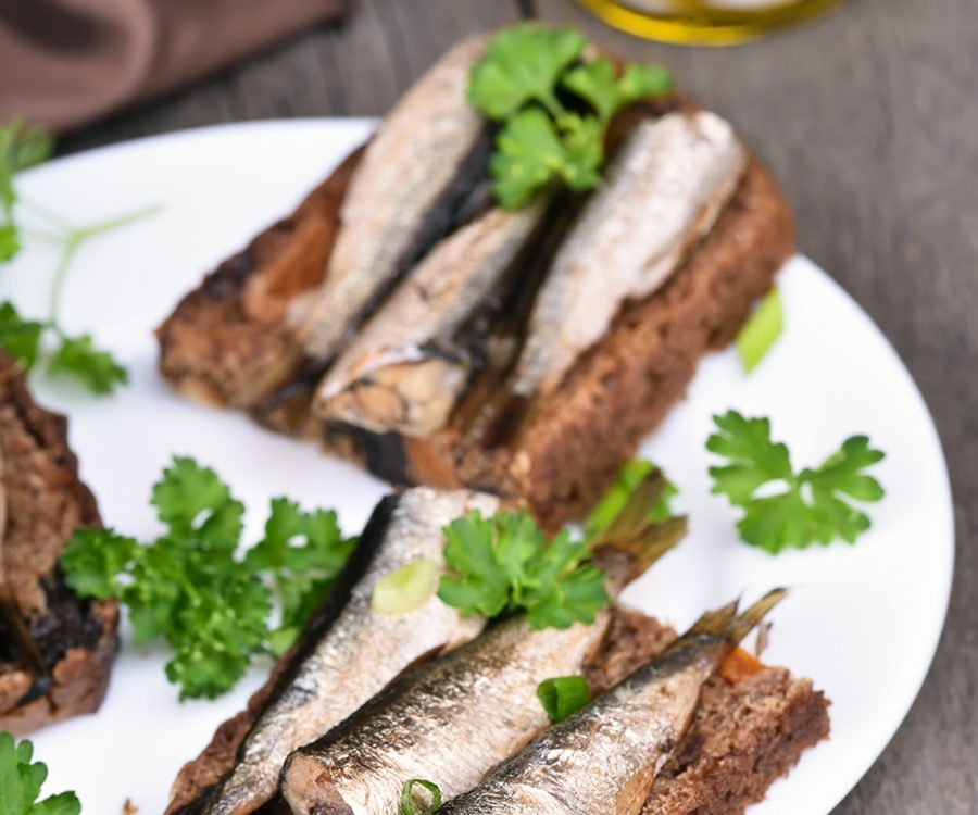 Appetizer bread with sprats on white plate, close up view