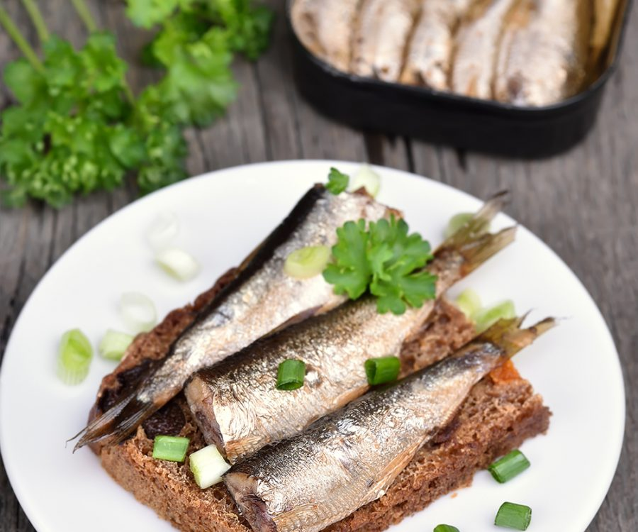 Sandwich with sprats and green onion on wooden table