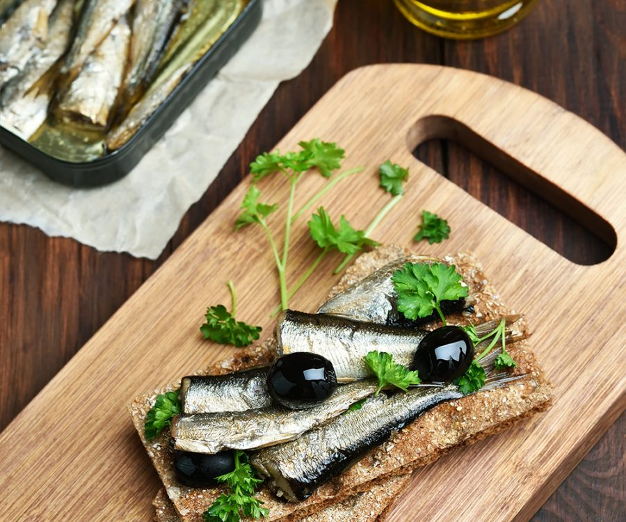 Crispbread with sprats and olives on wooden cutting board