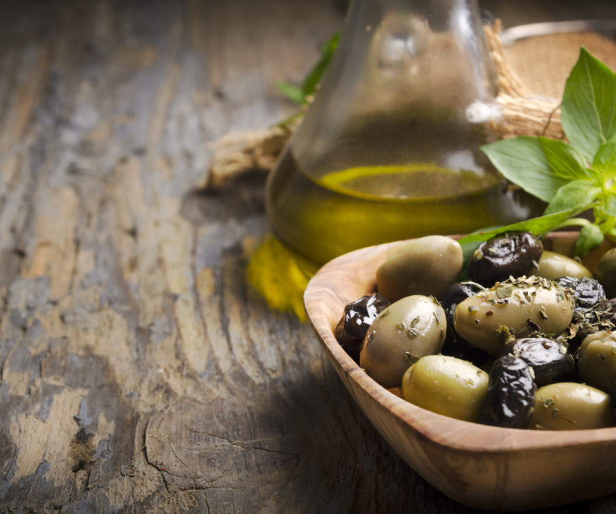 Olives and olive oil on rustic wooden table